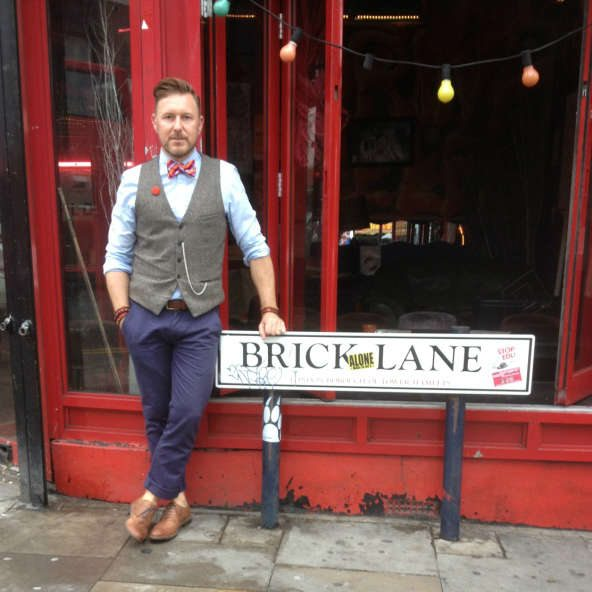 Dapper Chap standing by Brick Lane street sign