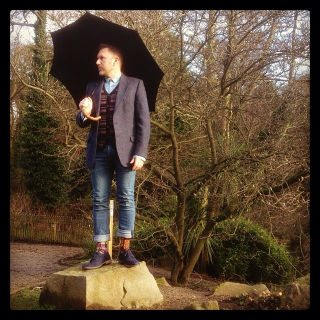 Well dressed man under vintage umbrella