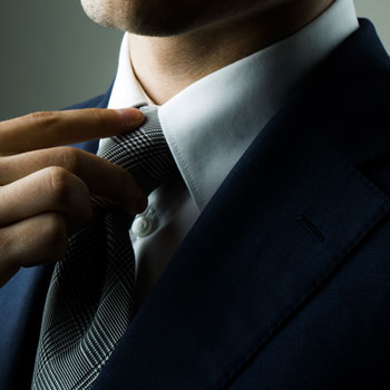A Fashionable Man In Suit & Straightening Tie July 2015