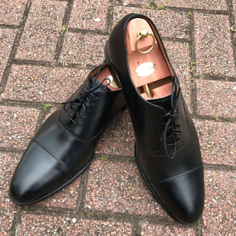 Black Cap Toe Shoes On brick