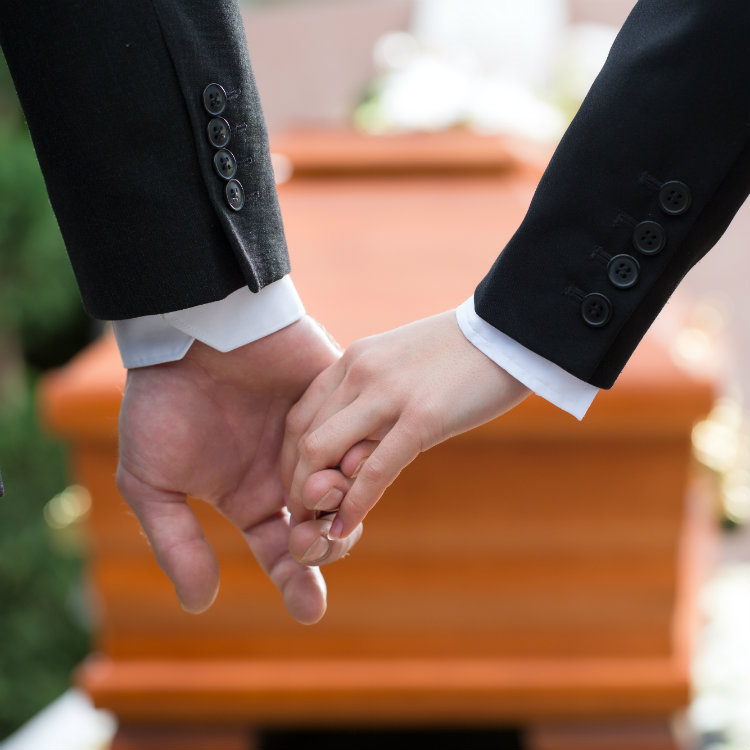 Two-People-Holding-Hands-At-Funeral