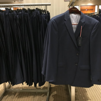 various suits on hangers in store