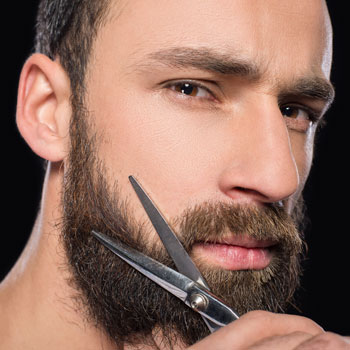 Man Trimming Beard With Scissors October