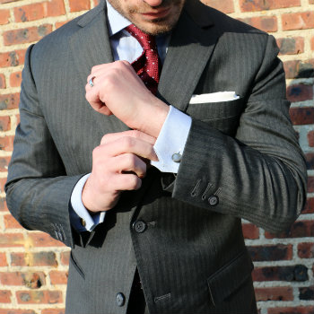 Man adjusting sleeve of power suit