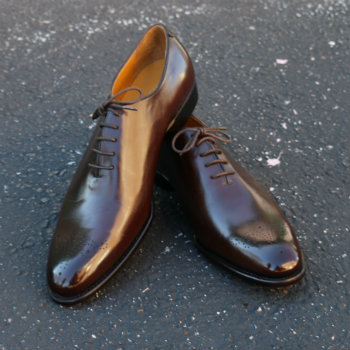 brown wholecut shoes on concrete