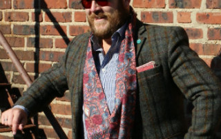 man in red paisley scarf and sport coat