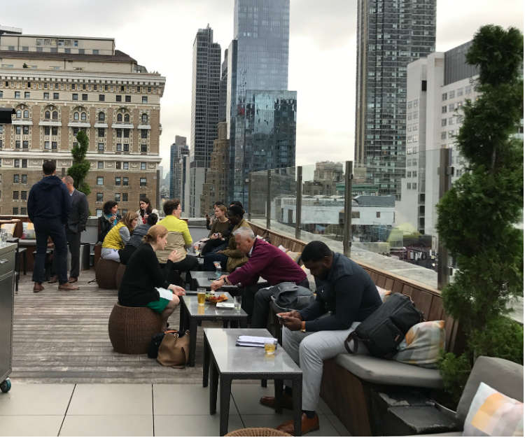 People On Patio Furniture At Rooftop Bar