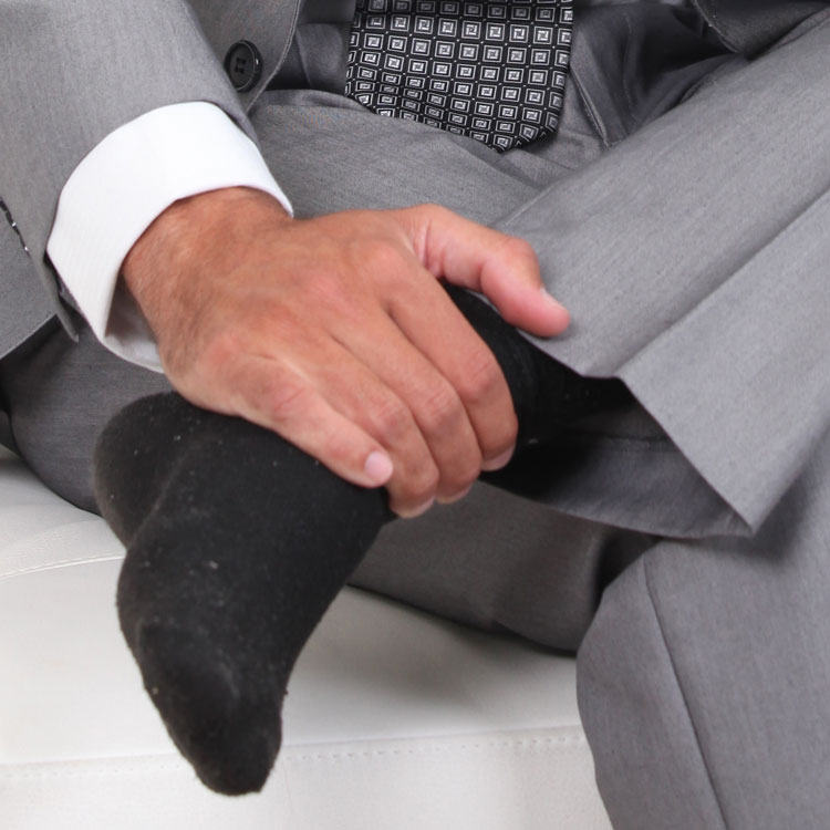 Man In Suit Rubbing Foot