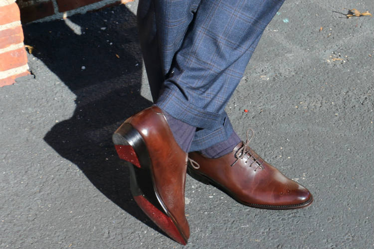 brown wholecut shoes with blue trousers
