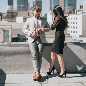 Man & Woman In Cocktail Attire On Rooftop